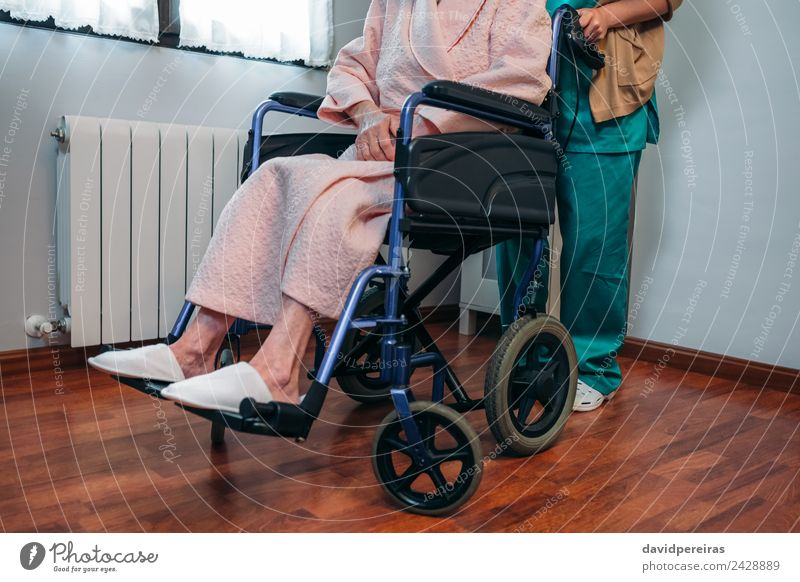 Doctor carrying elderly patient in a wheelchair Health care Illness Relaxation Hospital Human being Woman Adults Slippers Old Carrying Authentic Unrecognizable