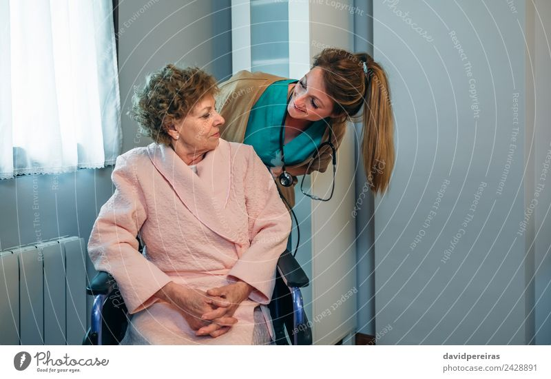 Doctor talking to elderly patient in a wheelchair Health care Illness Relaxation Bedroom Hospital To talk Human being Woman Adults Old Smiling Authentic
