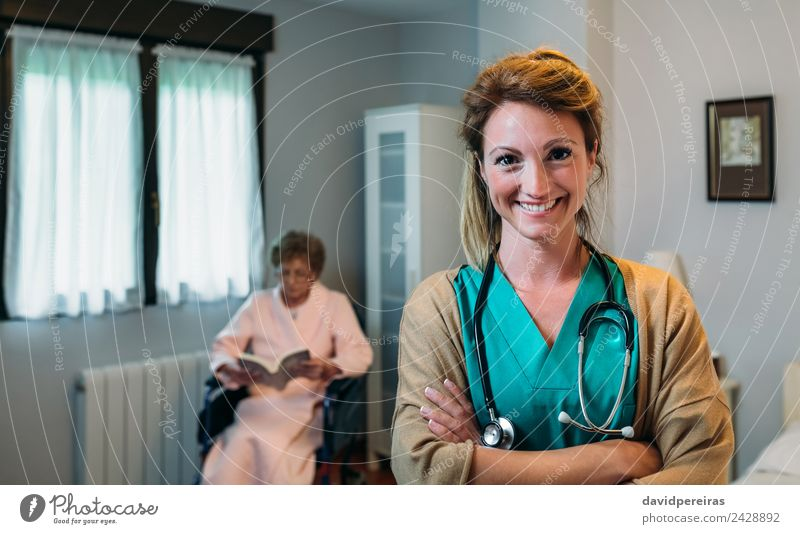 Pretty female doctor posing in a geriatric clinic Happy Health care Illness Relaxation Reading Bedroom Doctor Hospital Human being Woman Adults Old Smiling