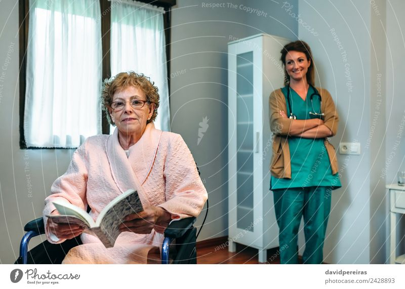 Senior patient posing with doctor in the background Health care Illness Relaxation Reading Bedroom Doctor Hospital Human being Woman Adults Book Old Smiling Sit