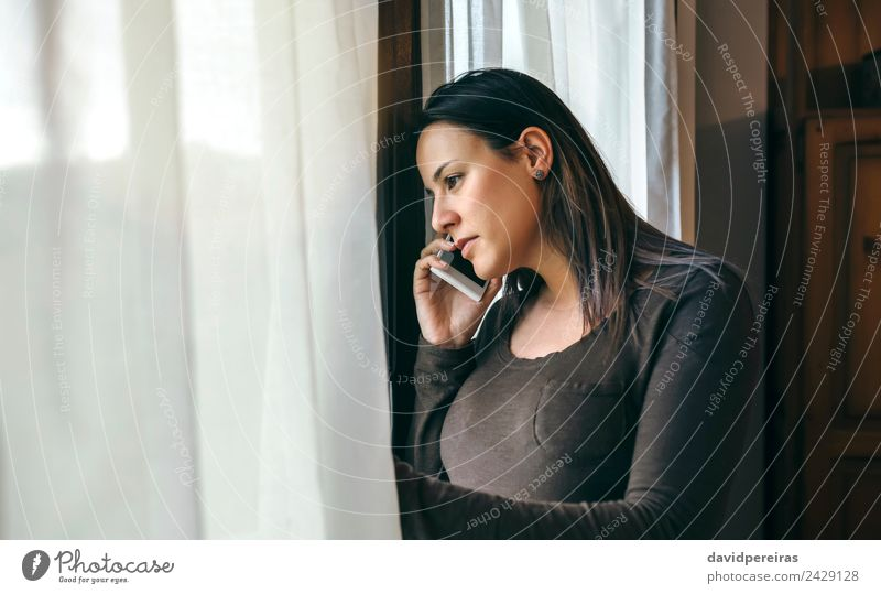 Woman talking cellphone and looking window Lifestyle Beautiful To talk Telephone PDA Human being Adults Sadness Wait Authentic Modern Cute sad Earnest mobile