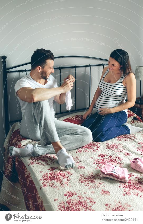 Man showing baby clothes to pregnant woman Woman Human being Beautiful Adults Emotions Family & Relations Couple Pink Sit Footwear Smiling Happiness Authentic