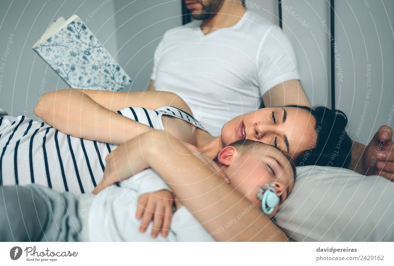 Man reading with wife and son sleeping Beautiful Relaxation Reading Bedroom Child Human being Baby Toddler Woman Adults Parents Mother Father Family & Relations