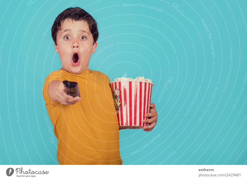 surprised boy with popcorn and television remote control Child Human being Joy Lifestyle Funny Emotions Boy (child) Food Leisure and hobbies Masculine Nutrition