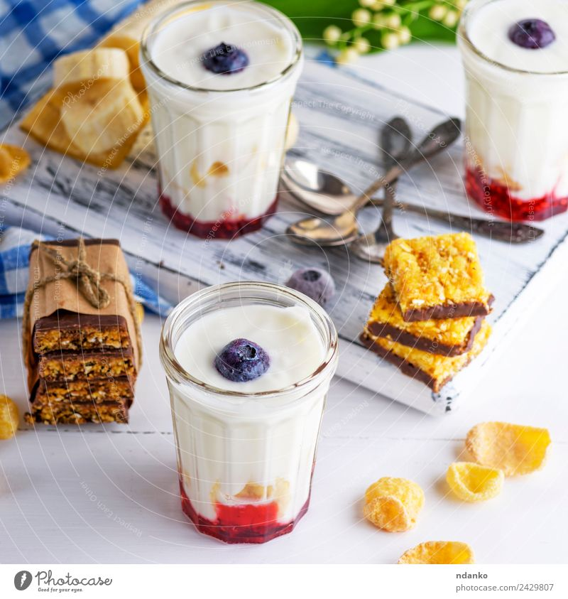 yogurt in transparent glass Yoghurt Dairy Products Jam Nutrition Breakfast Diet Beverage Cold drink Spoon Table Flower Wood Fresh Natural Above Blue White