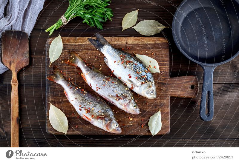 fish on a brown wooden board Fish Seafood Herbs and spices Nutrition Dinner Diet Pan Table Animal River Wood Dark Fresh Above Retro Brown Black Perches