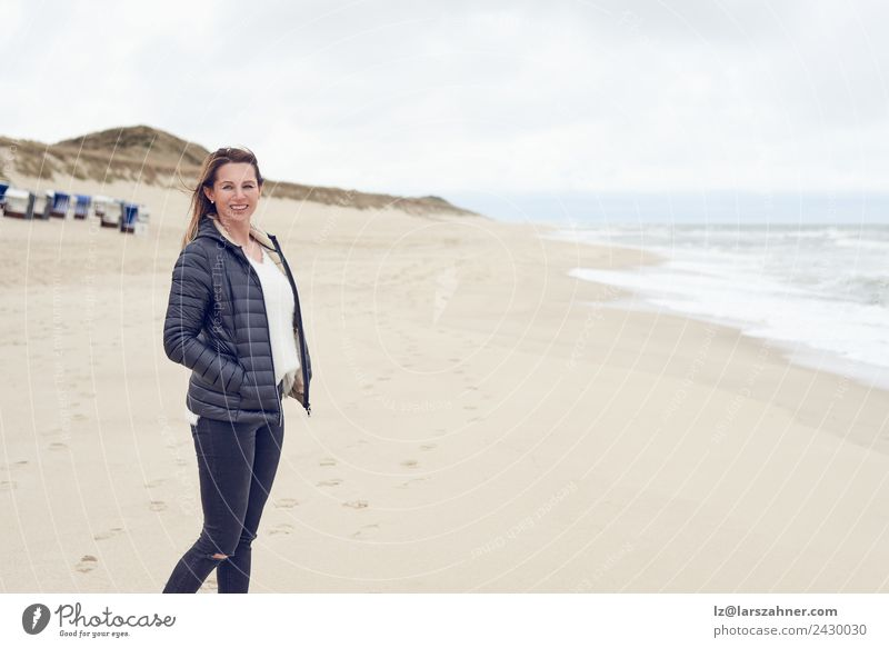 Woman walking on a beach on a cloudy day Leisure and hobbies Freedom Beach Ocean Adults 1 Human being 45 - 60 years Sand Clouds Autumn Coast North Sea