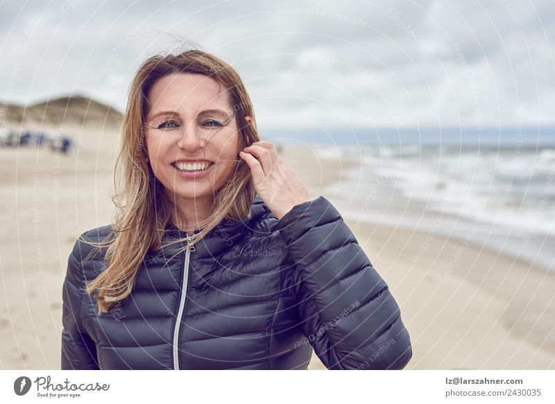 Attractive woman on a windswept beach Face Leisure and hobbies Freedom Beach Ocean Woman Adults 1 Human being 45 - 60 years Sand Clouds Autumn Storm Wind Coast
