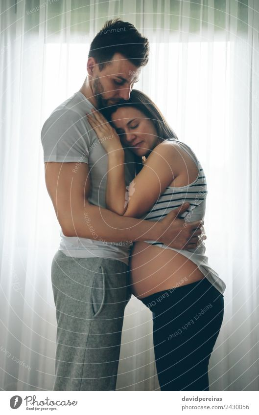 Pregnant woman embraced by her husband Lifestyle Beautiful Human being Baby Woman Adults Man Parents Mother Father Family & Relations Couple Partner Love