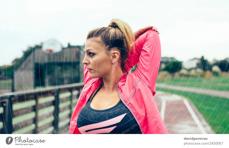 Young woman stretching arms before training outdoors Lifestyle Sports Jogging Racecourse Human being Woman Adults Arm Park Street Blonde Braids Line Fitness