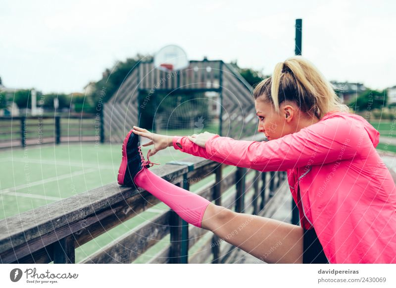 Young woman stretching legs before training outdoors Woman Human being Street Adults Lifestyle Sports Pink Line Park Blonde Action Authentic Arm Fitness