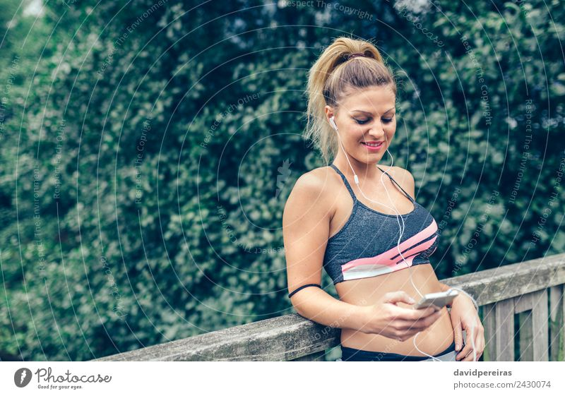 Woman in sports wear with earphones looking smartphone Lifestyle Joy Happy Music Sports Telephone PDA Technology Human being Adults Hand Blonde Braids Fitness