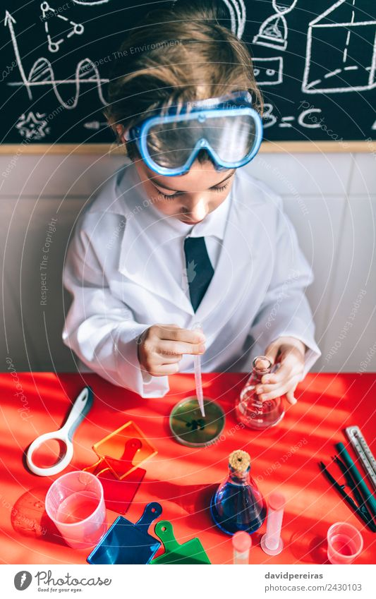 Serious kid playing with chemical liquids Bottle Playing Flat (apartment) Table Science & Research Child Classroom Laboratory Human being Boy (child) Infancy