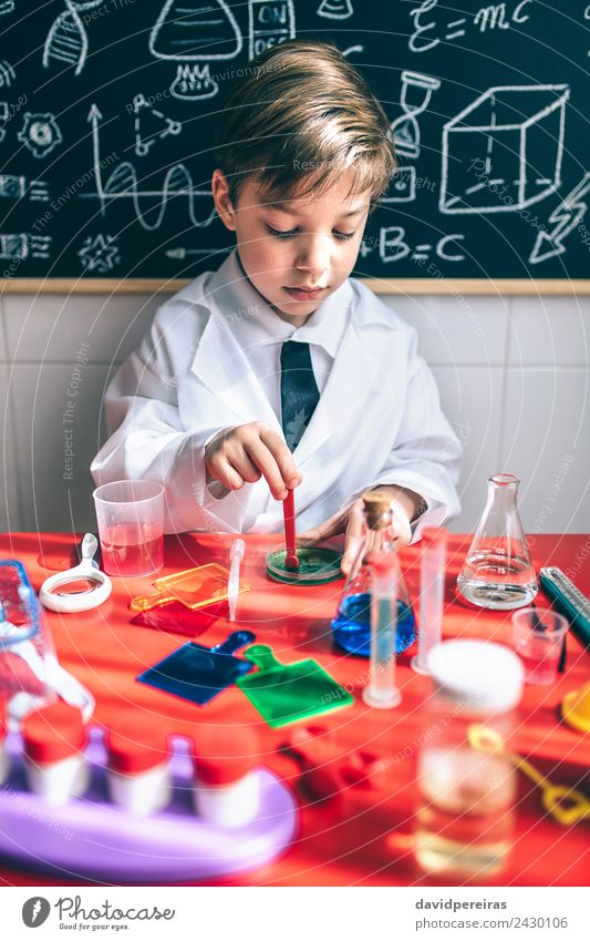 Kid playing to be chemist with colorful liquids Bottle Spoon Happy Playing Flat (apartment) Table Science & Research Child Classroom Blackboard Laboratory