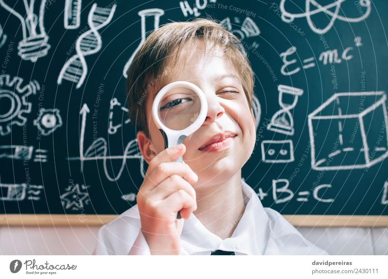 Little boy looking at camera through magnifying glass Joy Happy Playing Flat (apartment) Science & Research Child School Classroom Blackboard Laboratory