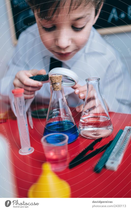 Happy kid looking liquid through magnifying glass Bottle Joy Playing Flat (apartment) Table Science & Research Child School Classroom Blackboard Laboratory
