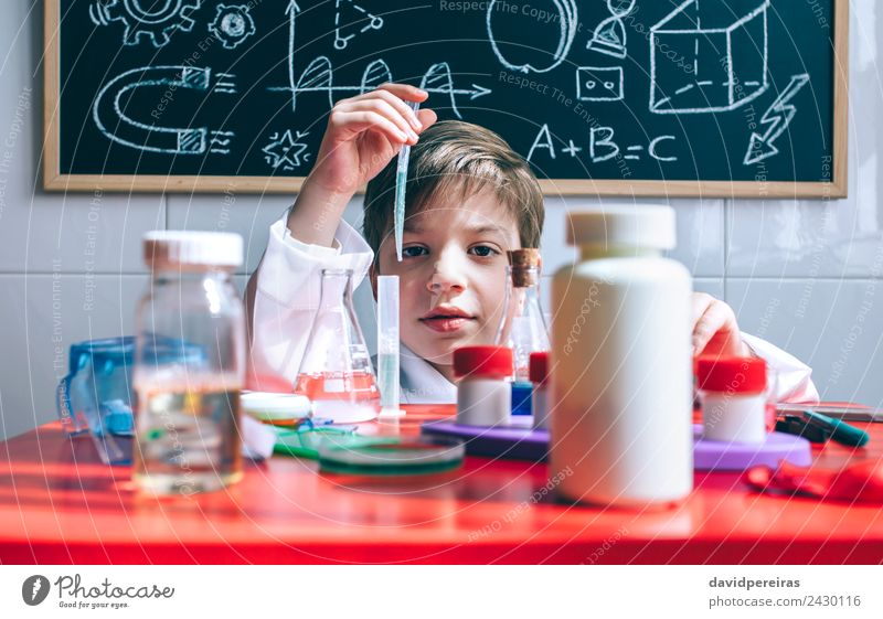 Kid playing with chemical liquids over table Bottle Happy Playing Flat (apartment) Table Science & Research Child Classroom Blackboard Laboratory Human being