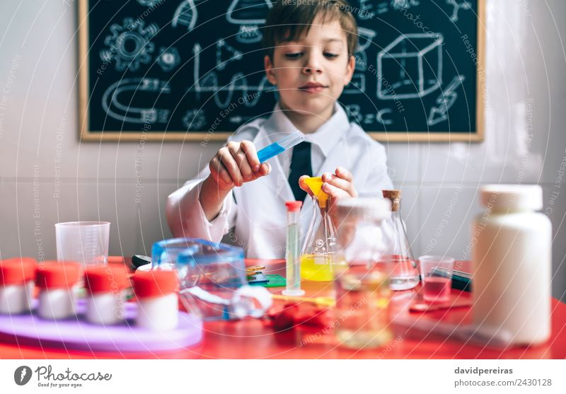 Serious little boy playing with chemical liquids Bottle Happy Playing Flat (apartment) Table Science & Research Child Classroom Blackboard Laboratory