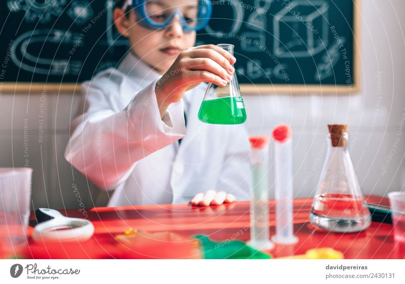 Little boy scientist with glasses holding flask against of blackboard Bottle Playing Flat (apartment) Table Science & Research Child Classroom Blackboard