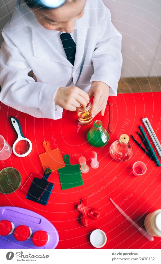 Little boy scientist mixing liquid in bottle Bottle Spoon Playing Flat (apartment) Table Science & Research Child Classroom Laboratory Human being Boy (child)
