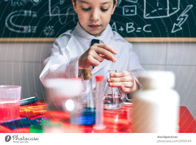 Serious kid playing with chemical liquids Bottle Happy Playing Flat (apartment) Table Science & Research Child Classroom Blackboard Laboratory Human being