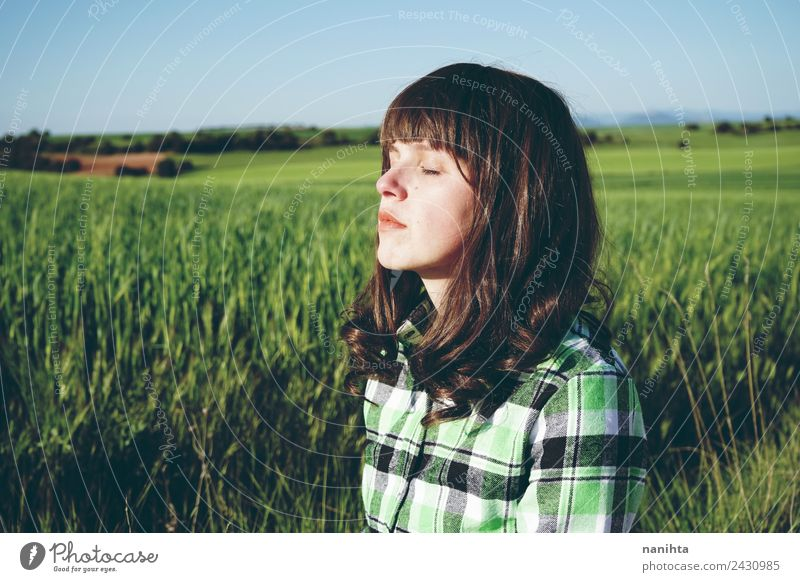 Young woman enjoying the sun in a green field Lifestyle Beautiful Healthy Harmonious Well-being Senses Relaxation Calm Meditation Agriculture Forestry