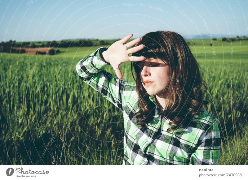 Young woman covering her face from sun in a green field Woman Human being Nature Youth (Young adults) Summer Beautiful Green Landscape Sun Relaxation