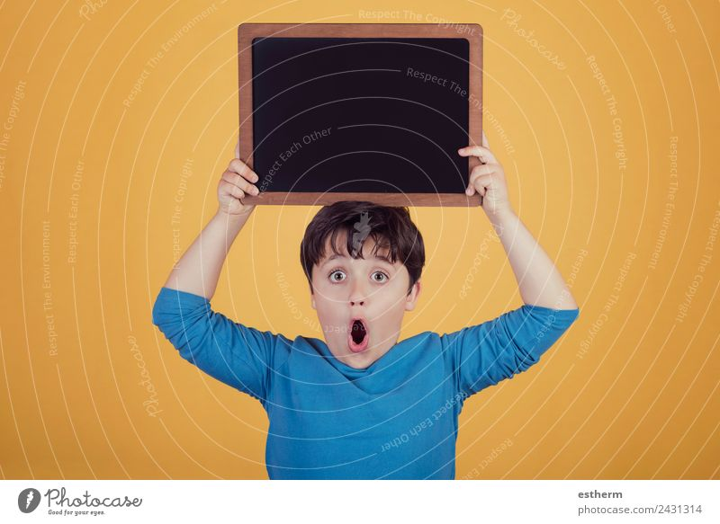 surprised boy with a blackboard Lifestyle Joy Human being Masculine Child Toddler Boy (child) Infancy 1 8 - 13 years Movement To hold on Fitness Smiling
