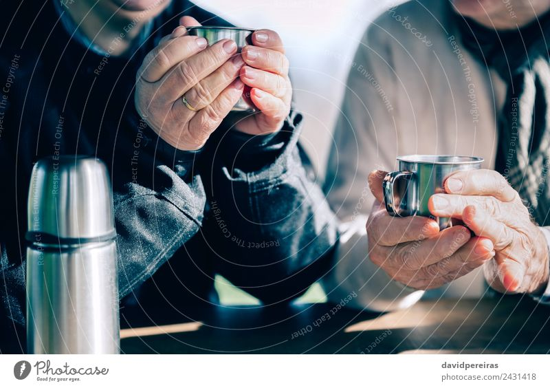Senior couple hands holding cups with hot coffee Coffee Tea Lifestyle Relaxation Leisure and hobbies Table Human being Woman Adults Man Couple Hand Warmth Wood