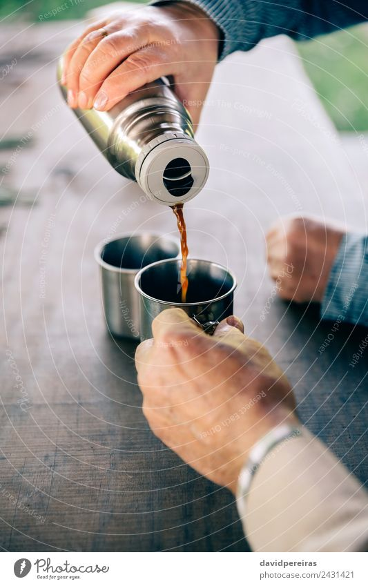 Senior couple hands pouring coffee from thermos Drinking Coffee Tea Lifestyle Relaxation Leisure and hobbies Table Human being Woman Adults Man Couple Hand Wood