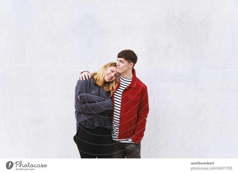 young couple in love in front of a concrete wall with free space for text Lifestyle luck Leisure and hobbies Human being Masculine Feminine Young woman