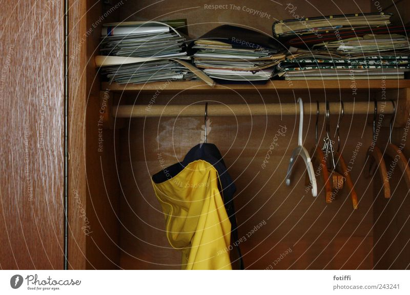 behind grandma's curtains V Jacket Far-off places Rain jacket Magazine Hanger Wood Rod Cupboard Yellow Brown Paper Past Memory Colour photo Interior shot