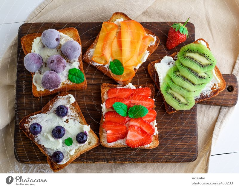 French toasts with soft cheese Cheese Fruit Bread Dessert Breakfast Wood Eating Above Soft Green Red White Strawberry kiwi Blueberry Dairy walnut persimmon