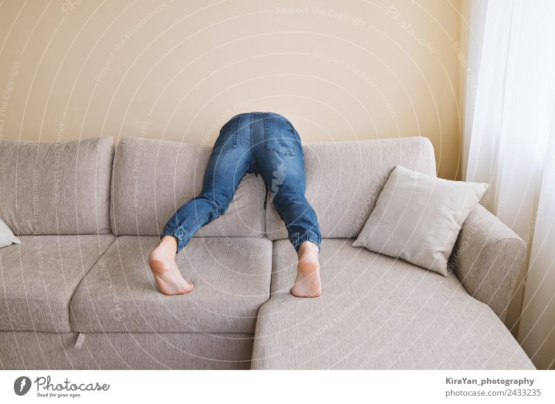 Man in jeans is cleaning behind sofa Lifestyle Relaxation Playing Furniture Sofa Hooligan Adults Father Bottom Feet Clothing Jeans Sadness Clean Stress Cozy