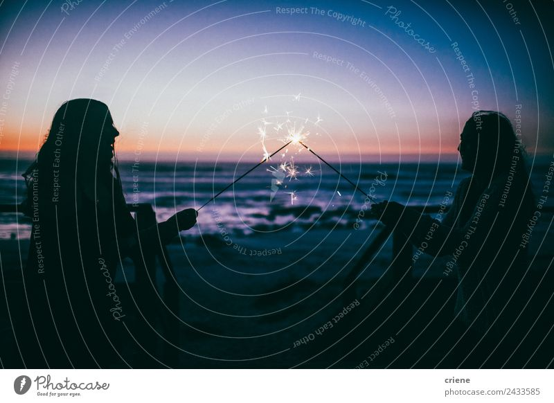 caucasian girlfriends holding sparkles by sunset at the coast Joy Happy Beautiful Summer Ocean Feasts & Celebrations Woman Adults Friendship Coast Smiling Love