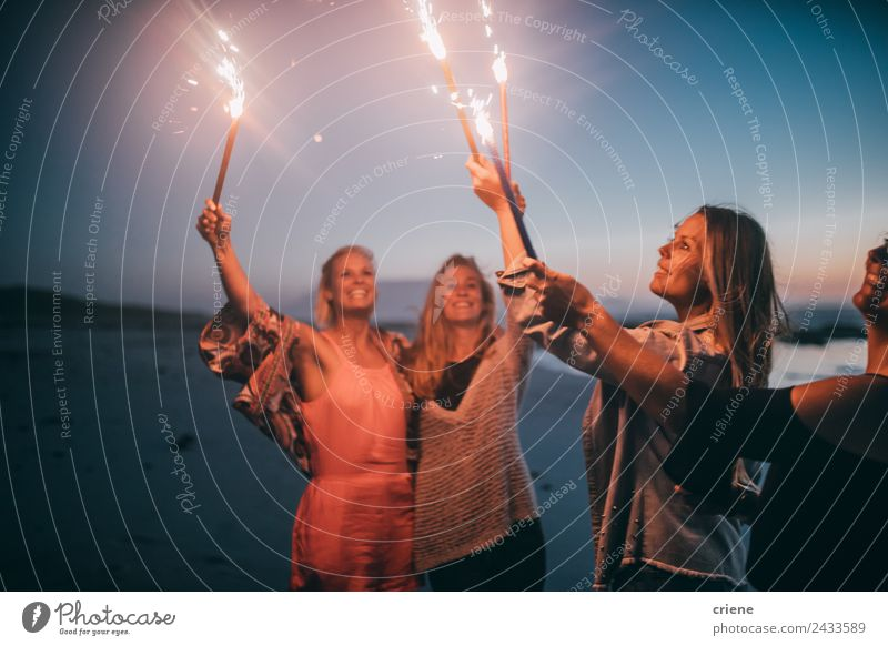 Group of friends celebrating New Years eve with sparklers Lifestyle Joy Happy Beautiful Summer Sun Beach Ocean Woman Adults Friendship Nature Sand Coast Blonde