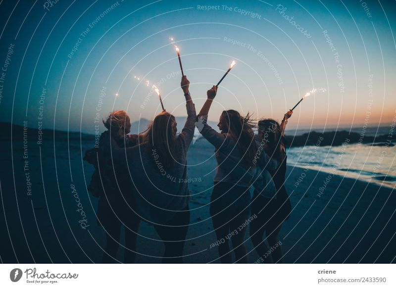 Happy group of girlfriends celebrating at beach with sparklers Woman Nature Summer Blue Beautiful Sun Ocean Joy Beach Adults Lifestyle Coast Laughter Together