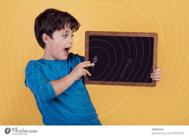 surprised boy with a blackboard Lifestyle Joy Education Child School Human being Masculine Boy (child) Infancy 1 8 - 13 years To hold on Fitness Smiling