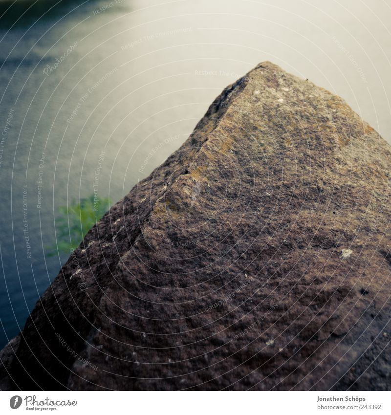 The rock in front of the water Environment Nature Elements Water Coast Lakeside River bank Blue Brown Green Stone Stony Reservoir Square Looking