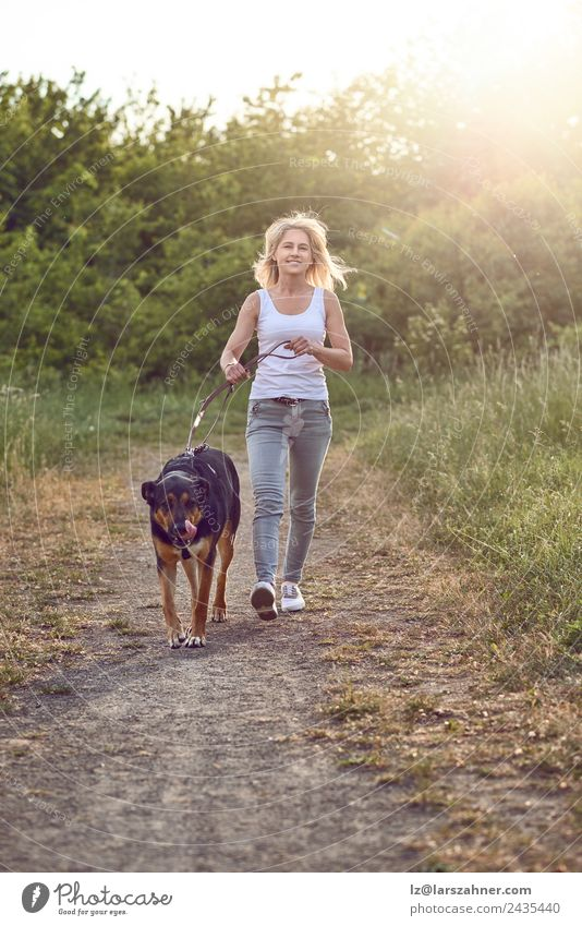 Happy middle-aged woman walking wiht her dog Woman Human being Nature Dog Summer Beautiful Animal Black Adults Warmth Lifestyle Grass Friendship Park Blonde