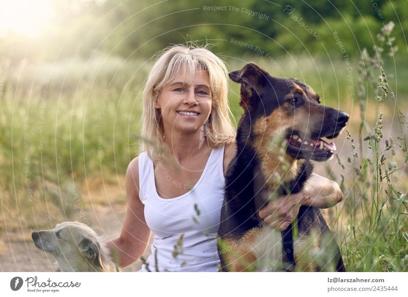 Pretty blond woman with her two dogs Happy Face Summer Woman Adults Friendship 1 Human being 45 - 60 years Animal Grass Meadow Blonde Pet Dog Smiling Love Sit