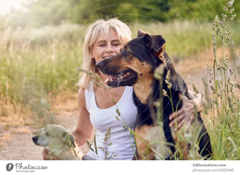Pretty blond woman with her two dogs Woman Human being Dog Summer Animal Face Adults Warmth Love Meadow Grass Happy Friendship Blonde Sit 45 - 60 years