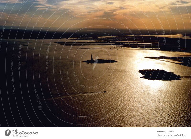 Statue of Liberty Sunset North America Water Sky Manhattan Atlantic Ocean Dusk Far-off places Horizon Aerial photograph Water reflection Silhouette