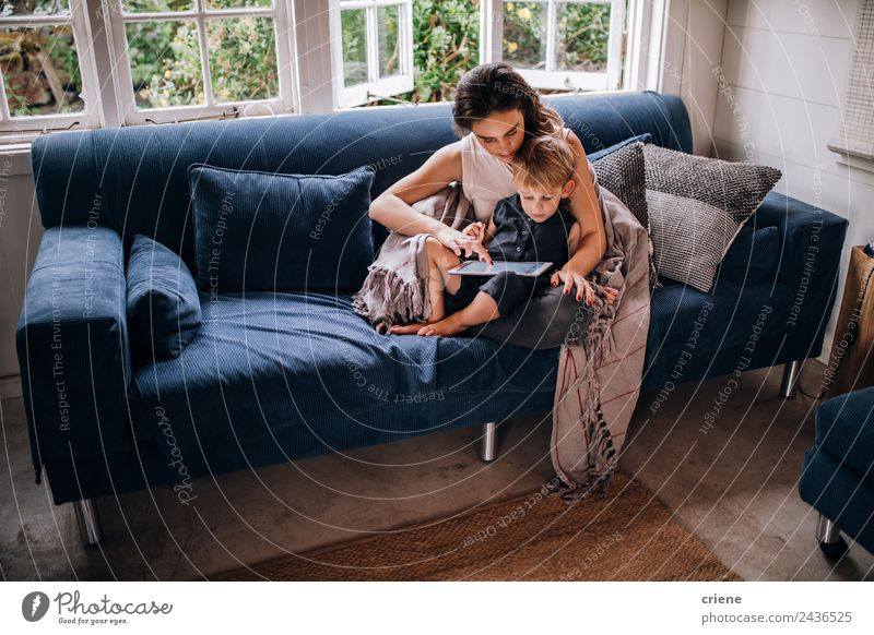 Caucasian mother and toddler son sitting on couch using tablet Lifestyle Joy Happy House (Residential Structure) Sofa Child Technology Toddler Woman Adults