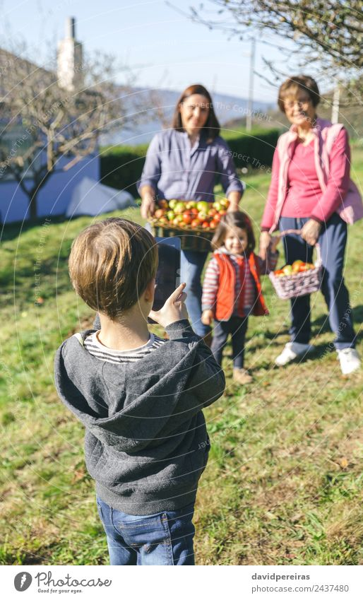 Boy taking photo to family with apples in basket Fruit Apple Lifestyle Joy Happy Leisure and hobbies Child Human being Boy (child) Woman Adults Man Mother