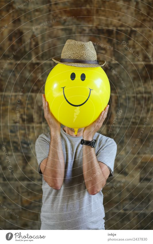 Eighth picture with yellow smiley Lifestyle Joy Leisure and hobbies Playing Man Adults Face 1 Human being 30 - 45 years 45 - 60 years Hat Straw hat Balloon Sign