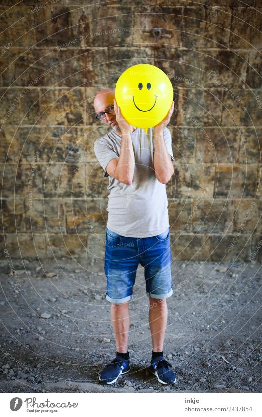 Third picture with yellow smiley Lifestyle Joy Leisure and hobbies Playing Man Adults 1 Human being 30 - 45 years 45 - 60 years Balloon Sign Smiley To hold on