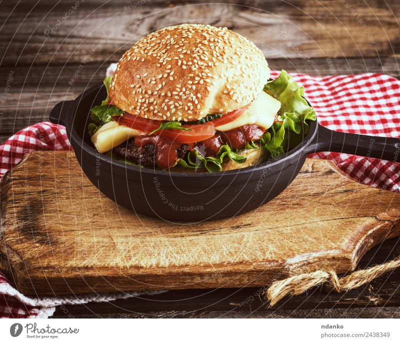 burger with a meatball Meat Cheese Vegetable Lettuce Salad Bread Roll Lunch Fast food Pan Table Wood Eating Fresh Large Delicious Green Red Black Hamburger Beef