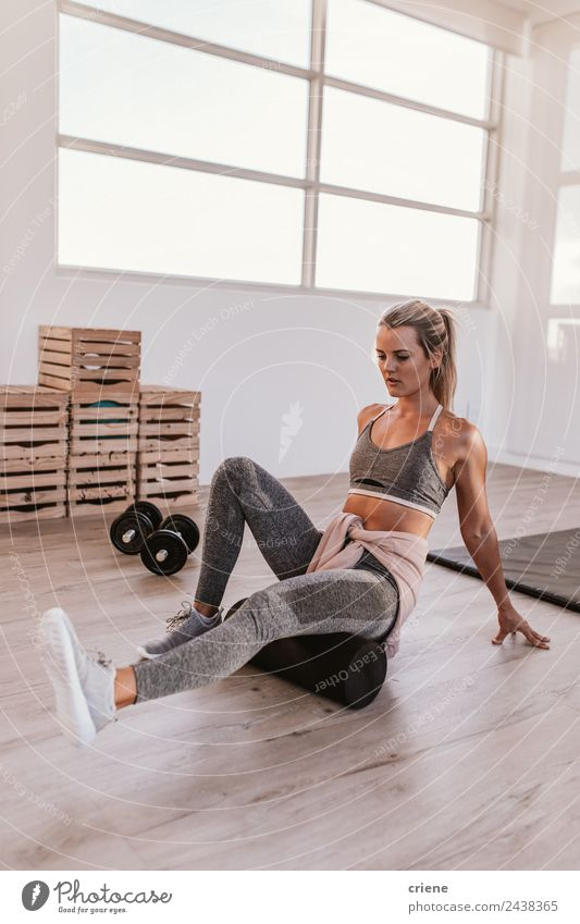 young woman foam rolling after exercise in gym Lifestyle Style Beautiful Body Sports Yoga Woman Adults Fitness Sit Athletic Thin Bright Power Concentrate