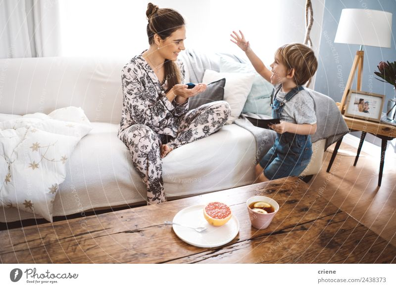 happy little boy giving gift to mother at home in living room Woman Child Beautiful Relaxation Adults Lifestyle Love Wood Family & Relations Laughter